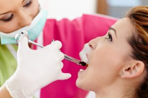 Closeup of a woman dentist giving her patient an anesthesia injection